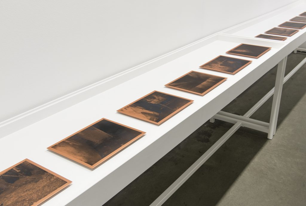 Copper coloured frames laid out on a table.