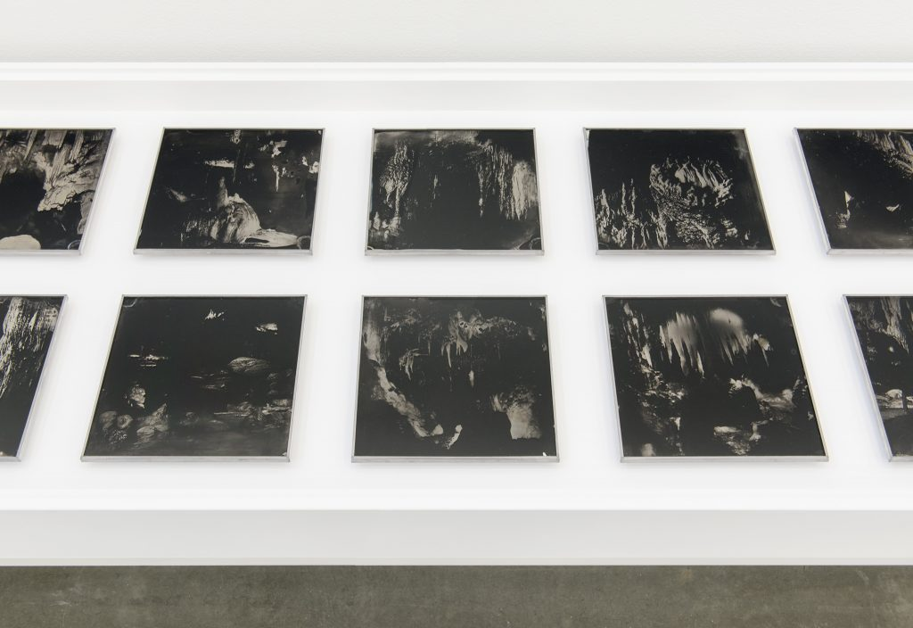 Several black and white square photographs of caves are laid out on a white table