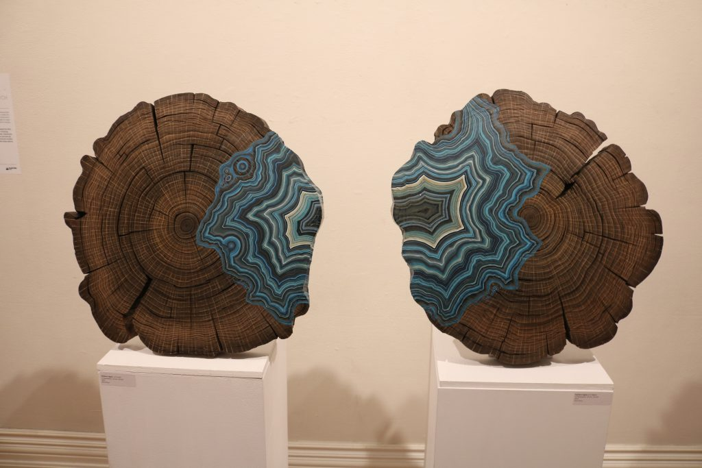 A newspaper sculpture resembling two tree stumps, with blue stripes painted on half of each of them.