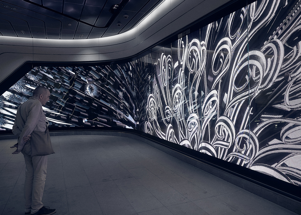 A man stands in front of Jon McCormack's video installation, The Unknowable