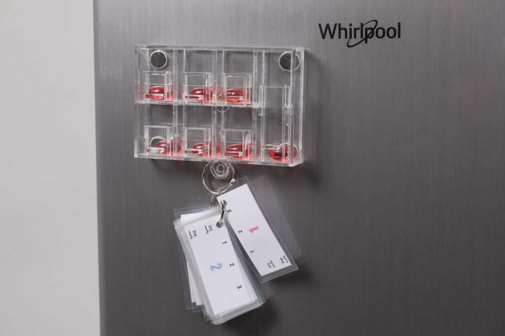 A fridge with a magnet holding medical pills