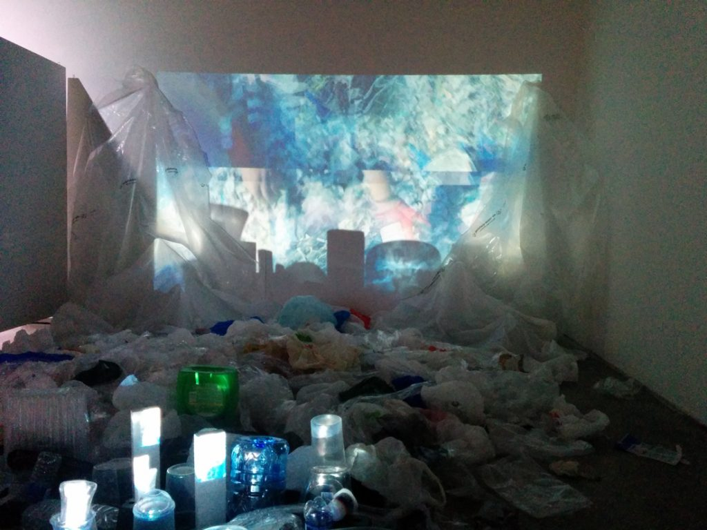 Heaps of discarded plastic make the backdrop for this sciart installation