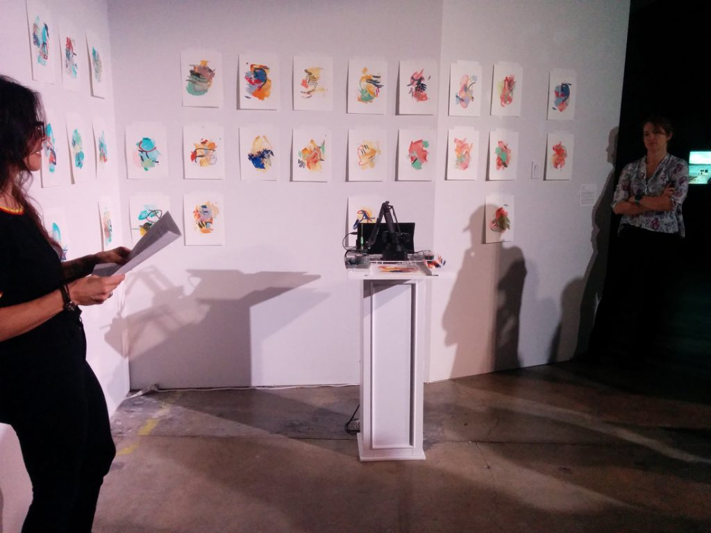A wall of paintings surrounds Joanne Hastie's artistic robot.