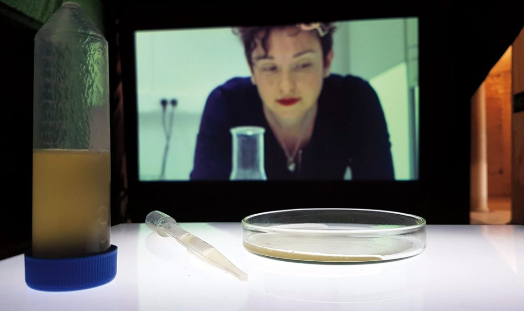 """A woman on a screen looks at the petri dish of """"female sperm"""" before her"""