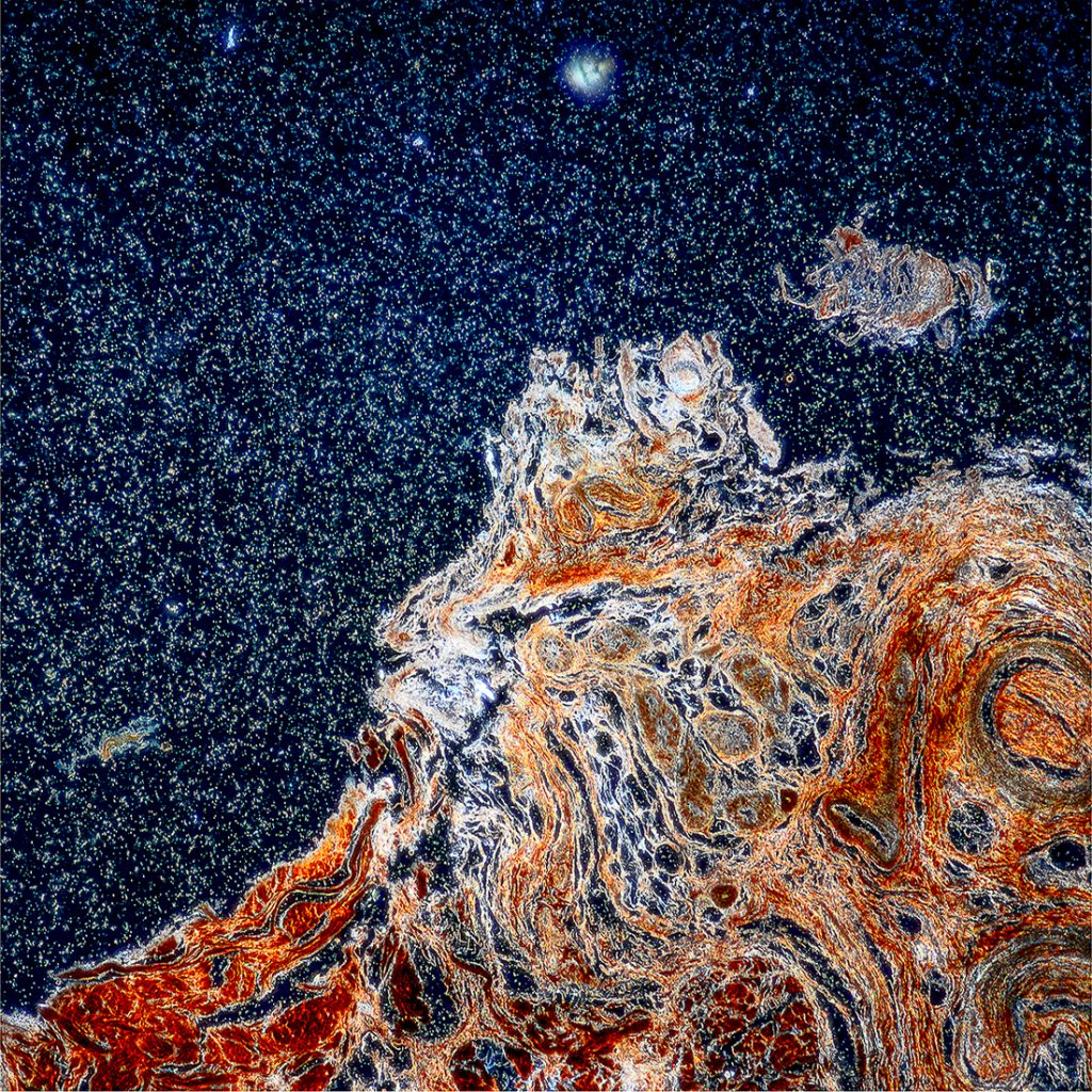 Half of the image is taken up by light blue-silver speckles on a dark background, which looks like a starry night sky. The other half contains swirls of shades of orange.