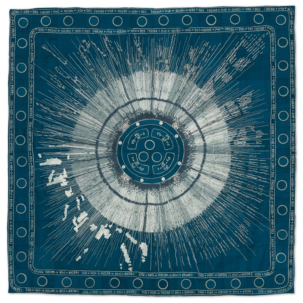 Large embroidered piece, looks like the sun on a blue background