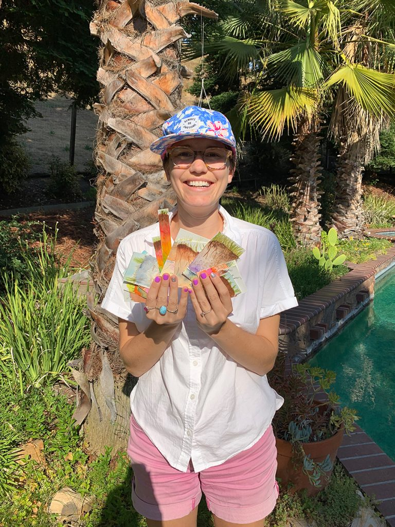Yamina Pressler wearing a white button down shirt, pink shorts, and a floral blue baseball cap holding some of her soil watercolors.