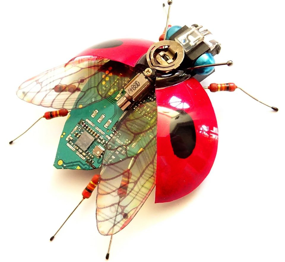 Lady bug with open wings made with circuit board components. It has hand painted wings fabricated from plastic bottles