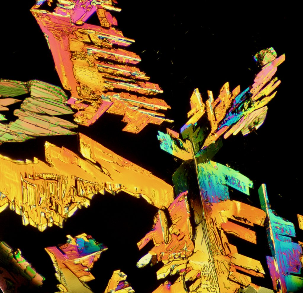 Jagged orange/iridescent crystal structures on a black background.