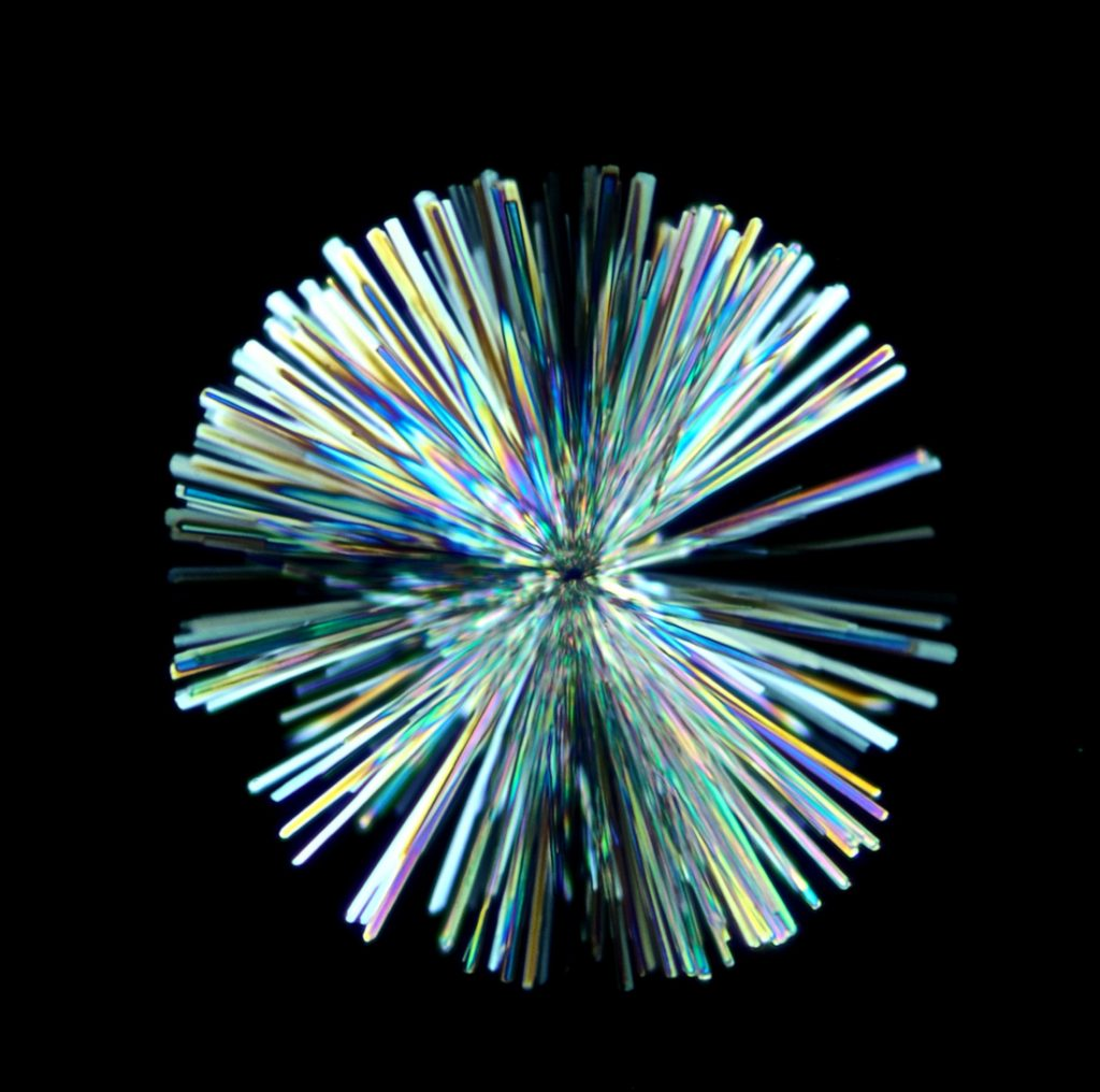 Iridescent rod-shaped crystals extending out of a single point to form a ball on a black background.