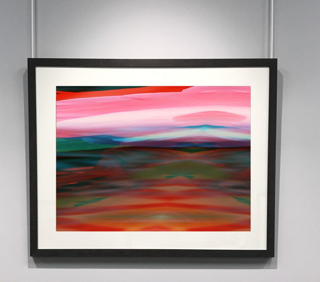 Framed image hanging on a white wall. Image looks like a pink dawn rising over a red and green landscape.