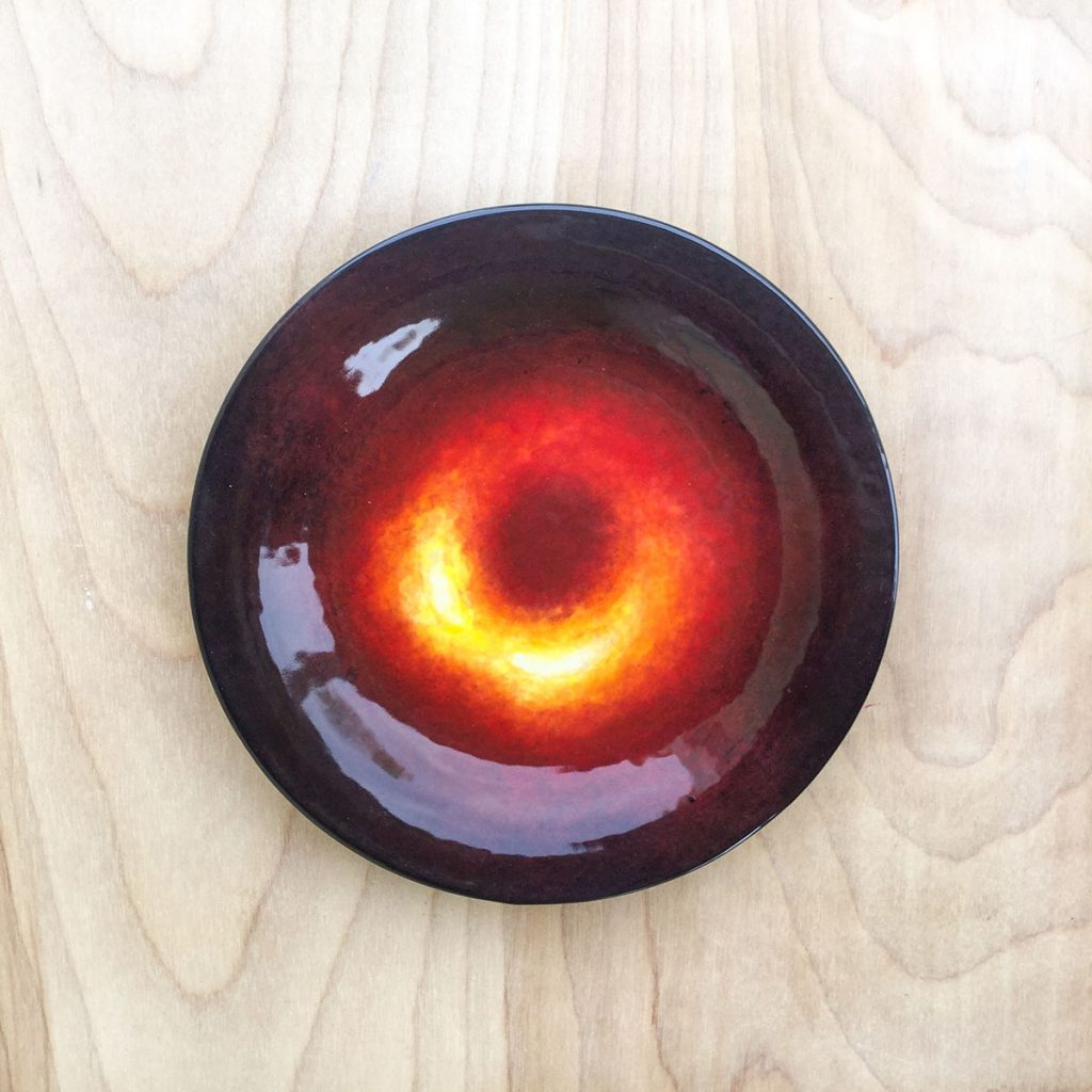 Ceramic plate featuring the first image of a black hole. The black hole is a yellowish-red donut shape with a black background.