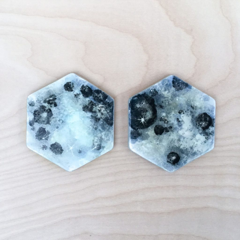 Two hexagon-shaped coasters that look like the surface of the moon