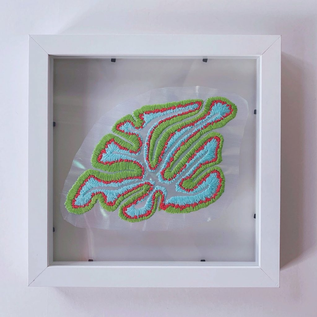 Framed embroidery applique piece of the cerebellum in green, blue, and red.