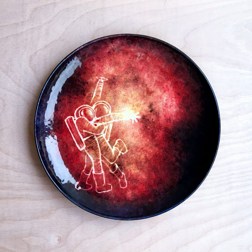 Ceramic plate with round red nebula and white outlines of two astronauts hugging