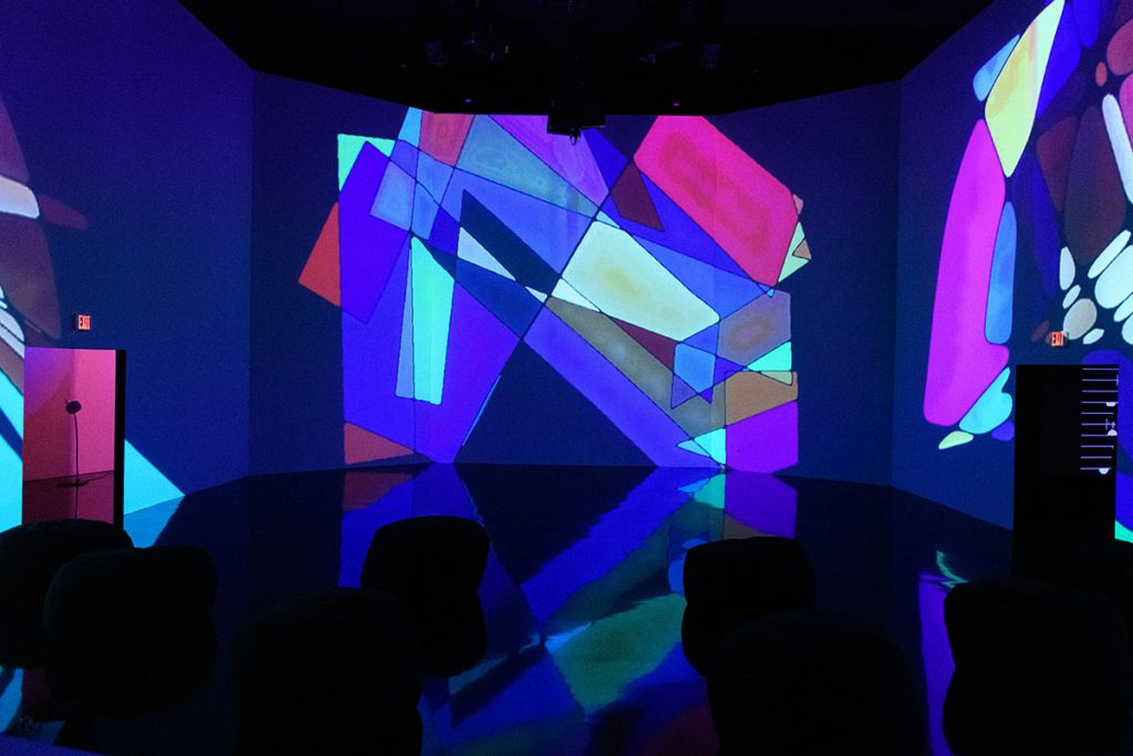 Colorful, geometric shapes are projected onto three large, open white walls in the dark exhibition space.