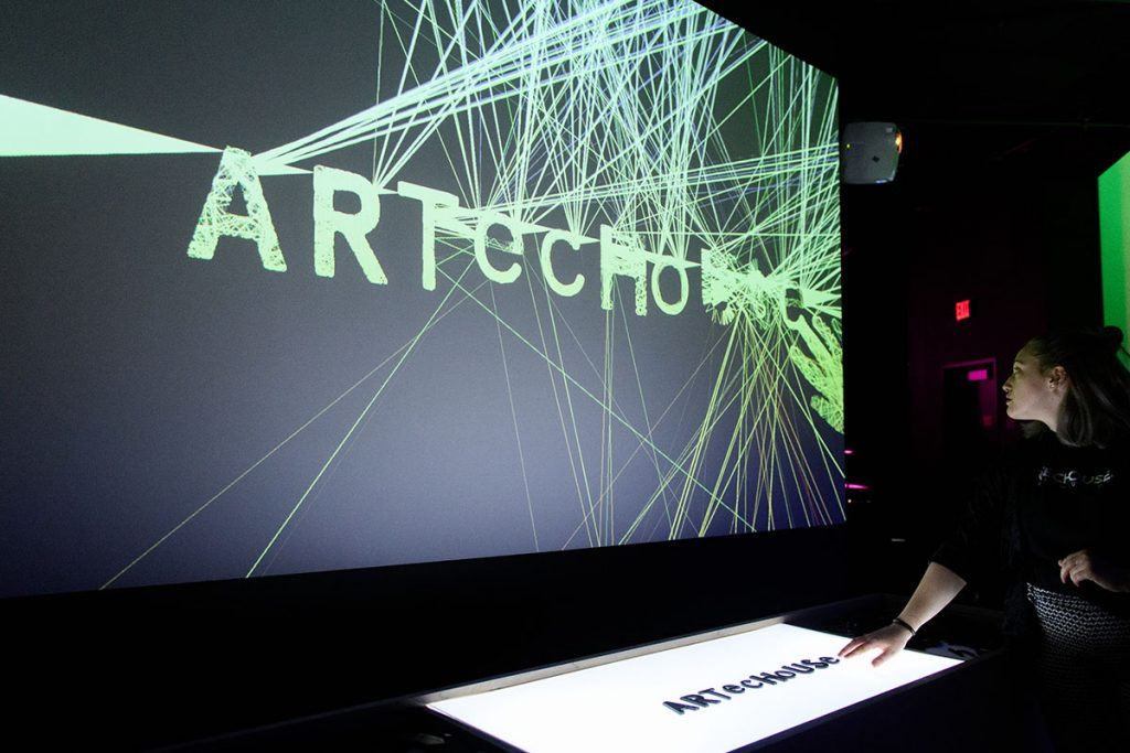 """Woman places plastic letters spelling """"Artechouse"""" on a backlit table. The letters are displayed on a screen with yellow lines bouncing off them."""