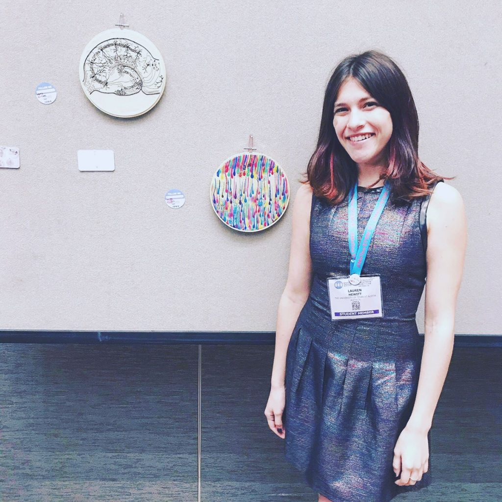 Lauren Hewitt standing by her artwork at the Society for Neuroscience 2018 annual meeting.