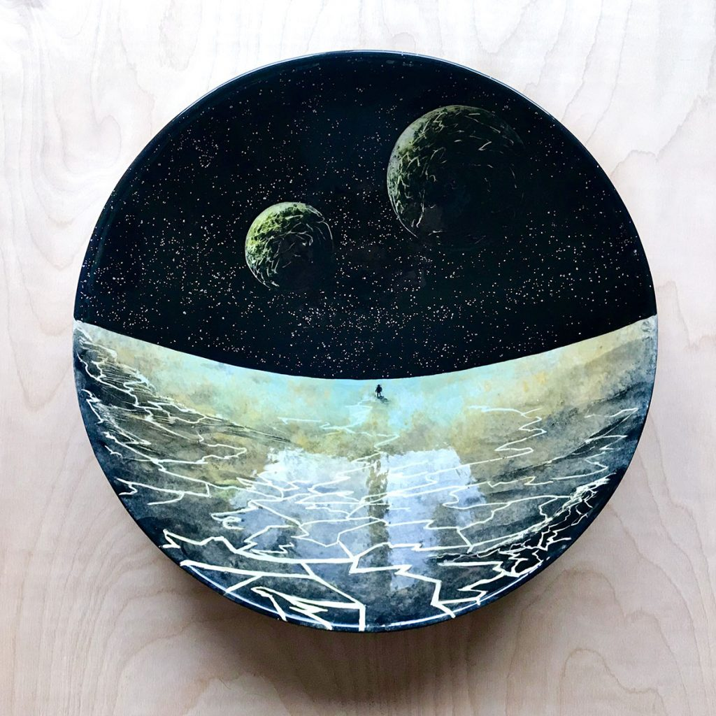 Ceramic bowl with the small figure of an astronaut standing on the surface of a moon cracking apart beneath them. There are large ominous cracks in the rock branching toward the space person, but they stand facing what's before them
