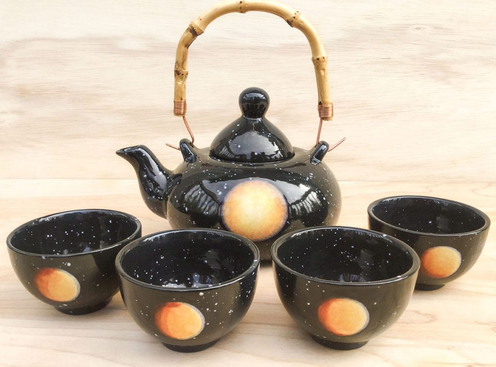 Japanese style tea set with a teapot that has a bamboo handle and four rounded teacups without handles. Each piece features the moon Titan surrounded by the black sky and white stars.