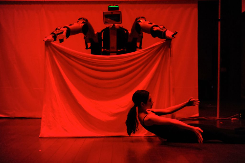A large robot holds up a white sheet while Catie dances on the floor in front of the sheet.