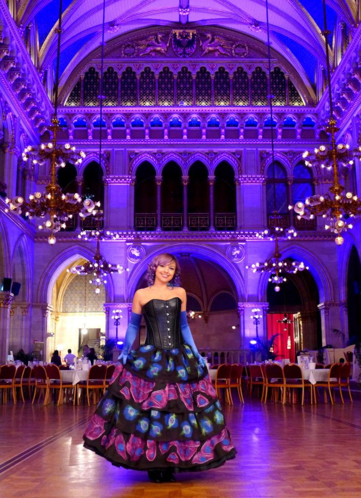 Beata wearing her microscopy dress, which has a black corset top and multiple tiers on the skirt. The tiers have alternating blue cells and pink cells.