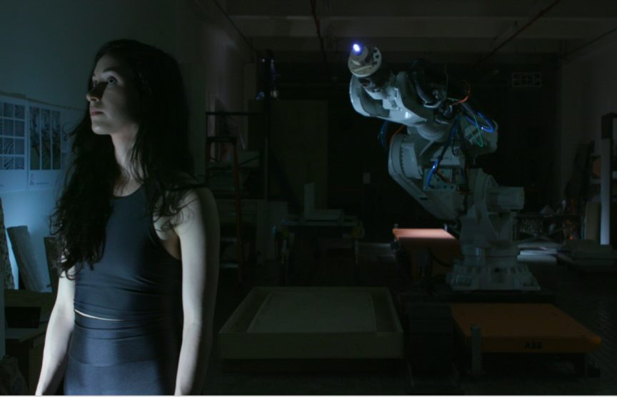 Catie stands in a dark room in front of a large robot. Still from OUTPUT project.