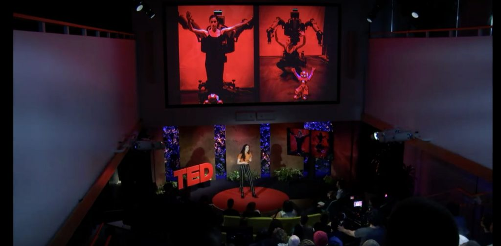 Catie talking on the TED talk stage. Above her are large images from her projects.