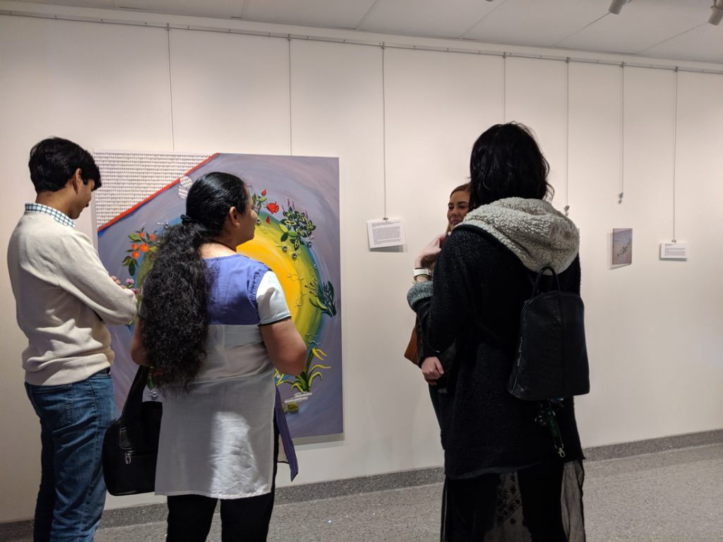 People looking at the sciart on display as part of the exhibition.