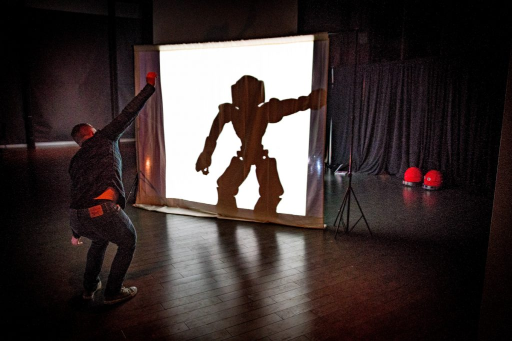 Participant posing in front of an illuminated screen with their arm out. Behind the screen, you can see the silhouette of a robot mimicking the participant's pose.