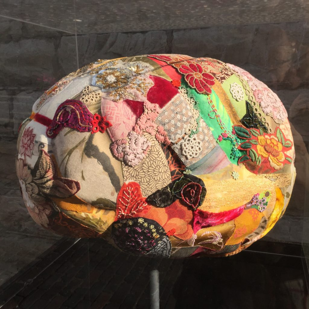 Three dimensional structure of a brain made with different fabrics and other materials.