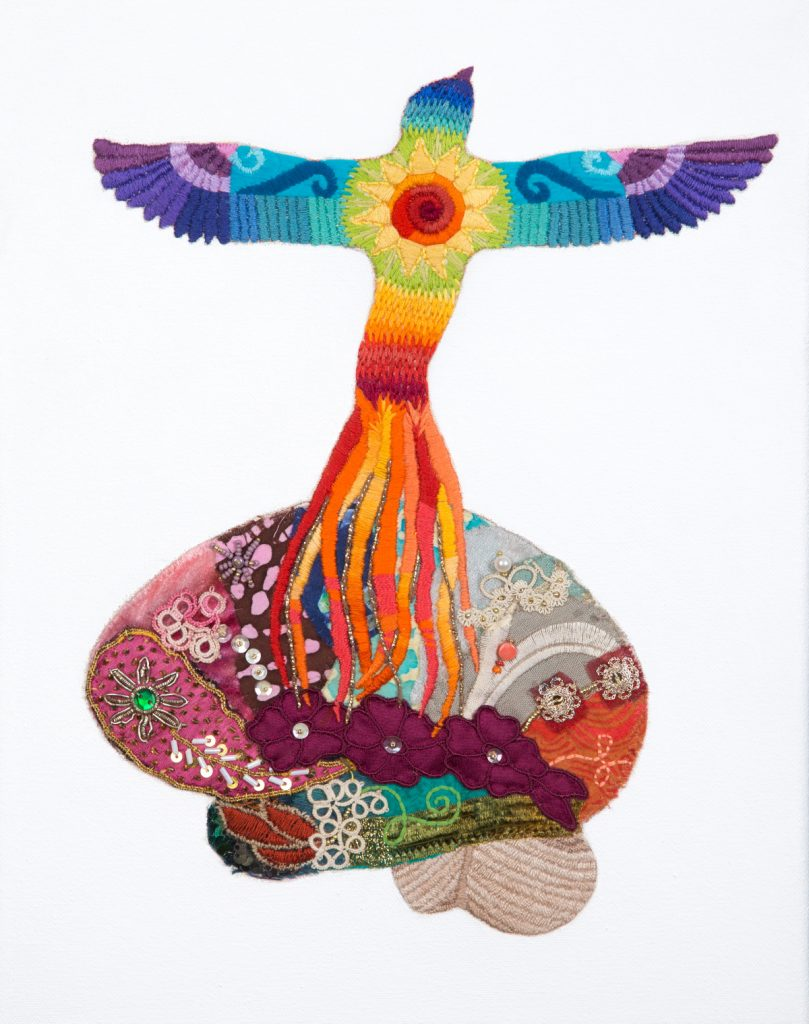 Colorful embroidered phoenix rising from a colorful brain made of different fabrics and materials.