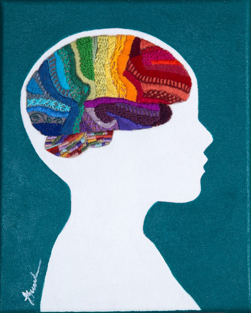 Colorful embroidered brain within a white side profile of a head.