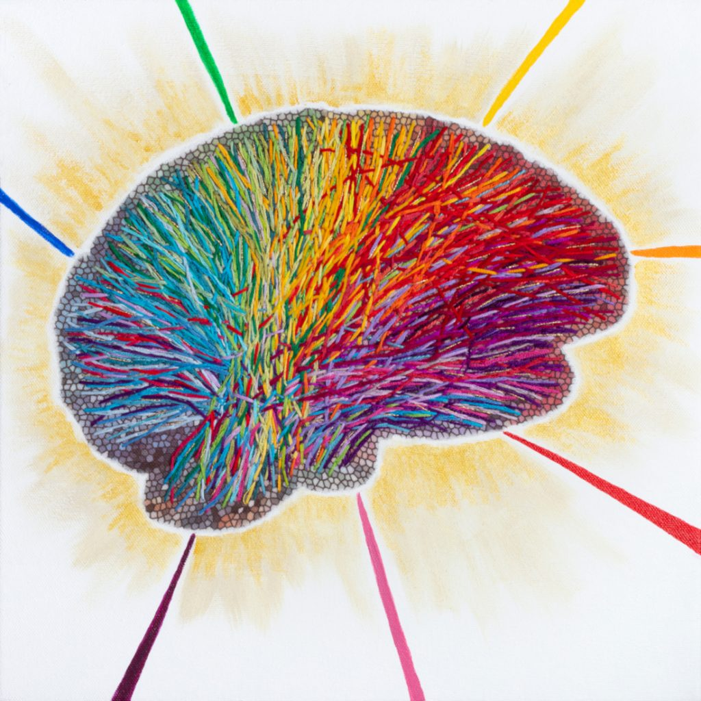 Colorful embroidered brain with rays of light and rainbow coming out of it.