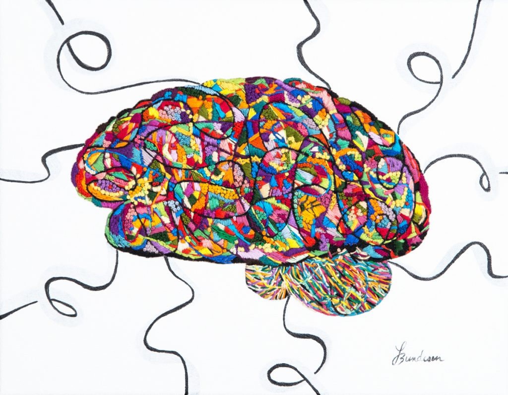 Brain embroidered with small patches of different colors. A few black spirals are coming out of the brain.