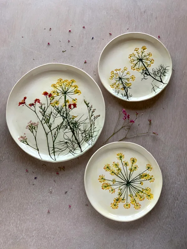 Three white plates with imprints of dill flowers. The flowers have been painted yellow, red, and pink.