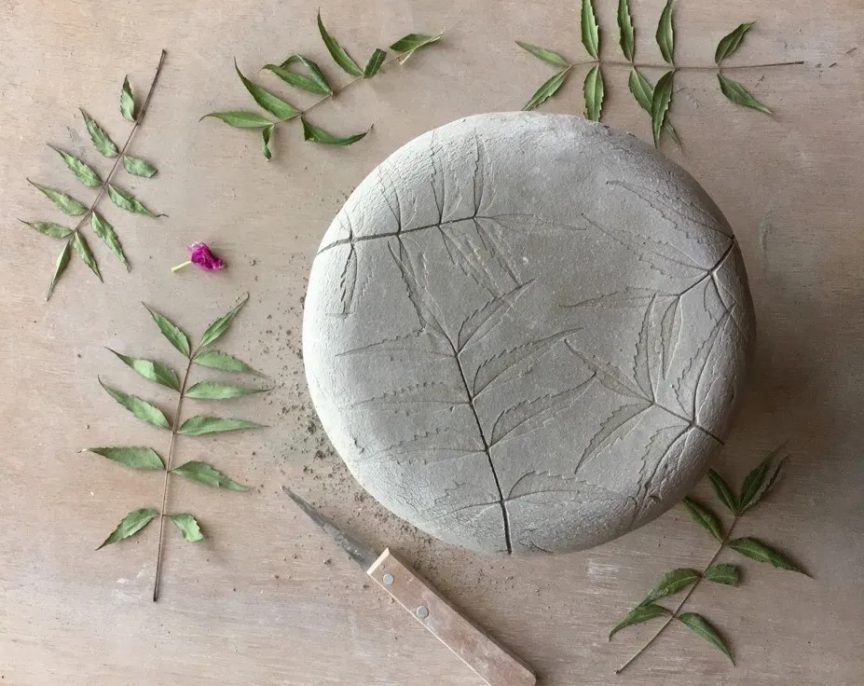 Round clay slab with leaves imprinted into it. In the background are the leaves that were pressed and a knife.