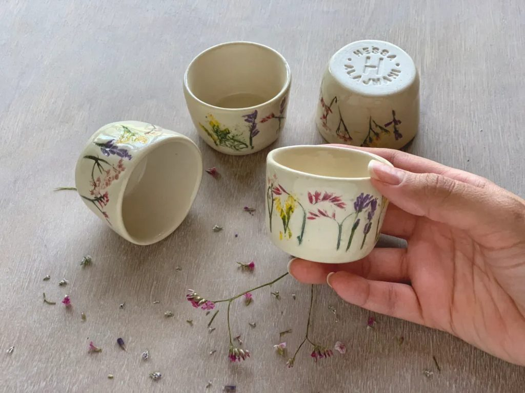 Four mall white cups without handles with painted imprints of flowers.