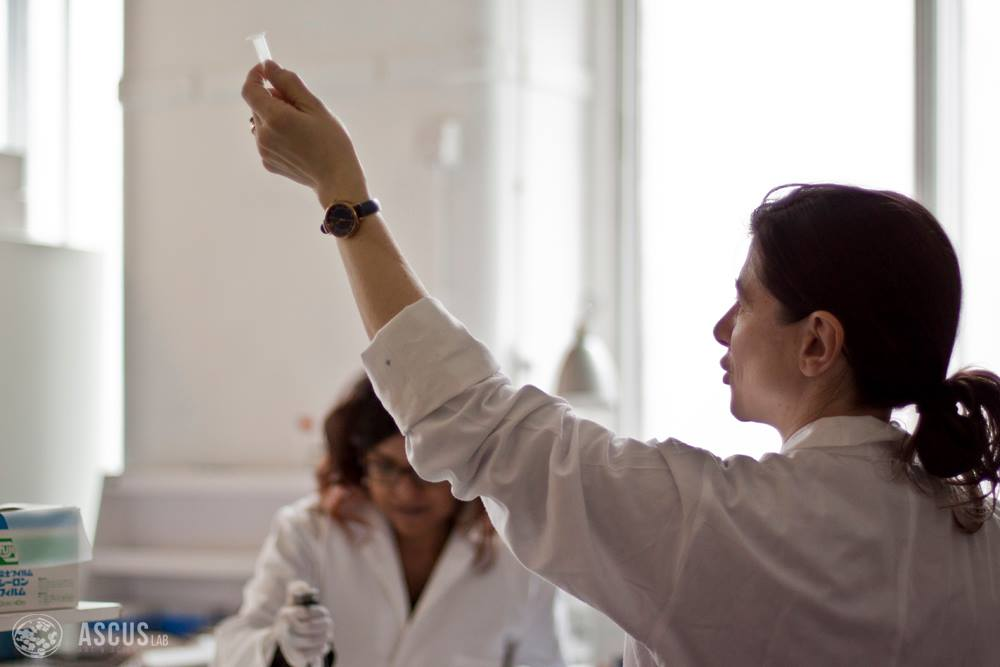 Woman wearing a lab coat holds up a small tube.