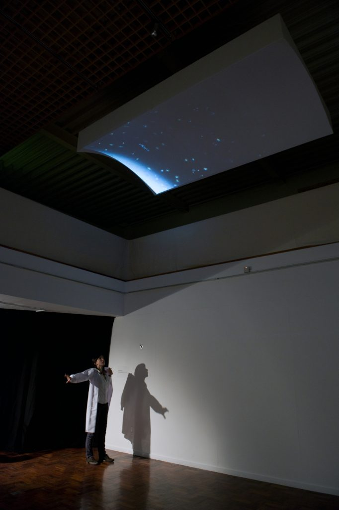 Woman stands beneath a panel mounted on the ceiling. The panel has blue micro-algae, which looks like fuzzy dots, projected onto it.
