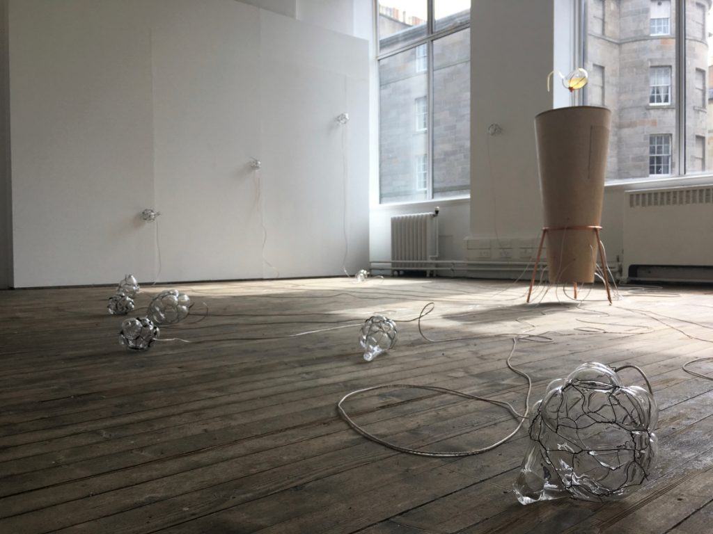 Blown glass containers with large, bubble-like structures wrapped with thick metal wire are strewn on a hardwood floor.