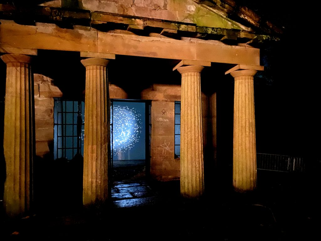 Video still of a glowing orb emitting light and sparkles. Video is displayed on the entrance of a building that looks like an ancient Greek building.