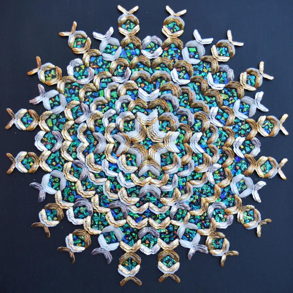 Circular form made of small, iridescent blue, green, and orange fragments and patterns of gold and silver feather-shaped pieces.