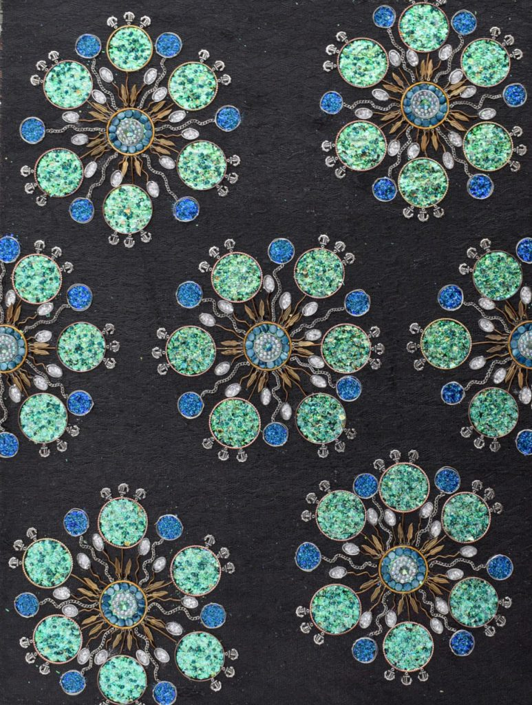 Delicate metal chains and blue and green glittering circles form flower-like shapes.