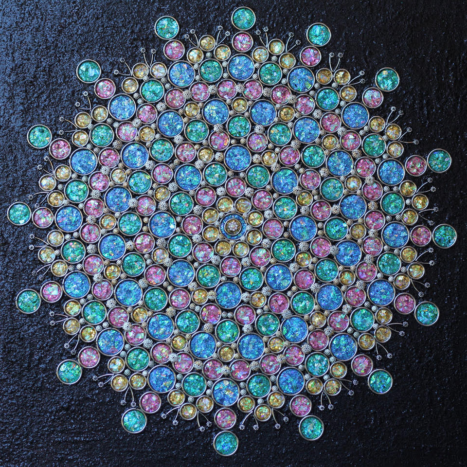 Pink, yellow, green, and blue glittering circles tightly compacted into a blooming flower shape.