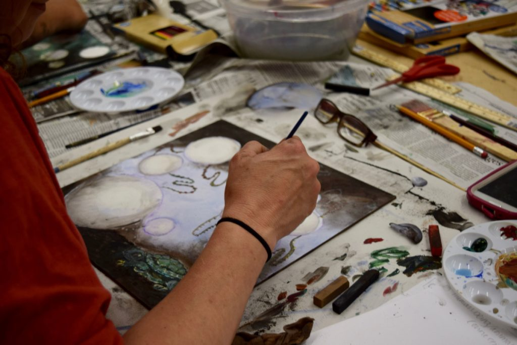 Image of a person's arm while painting at a workshop.