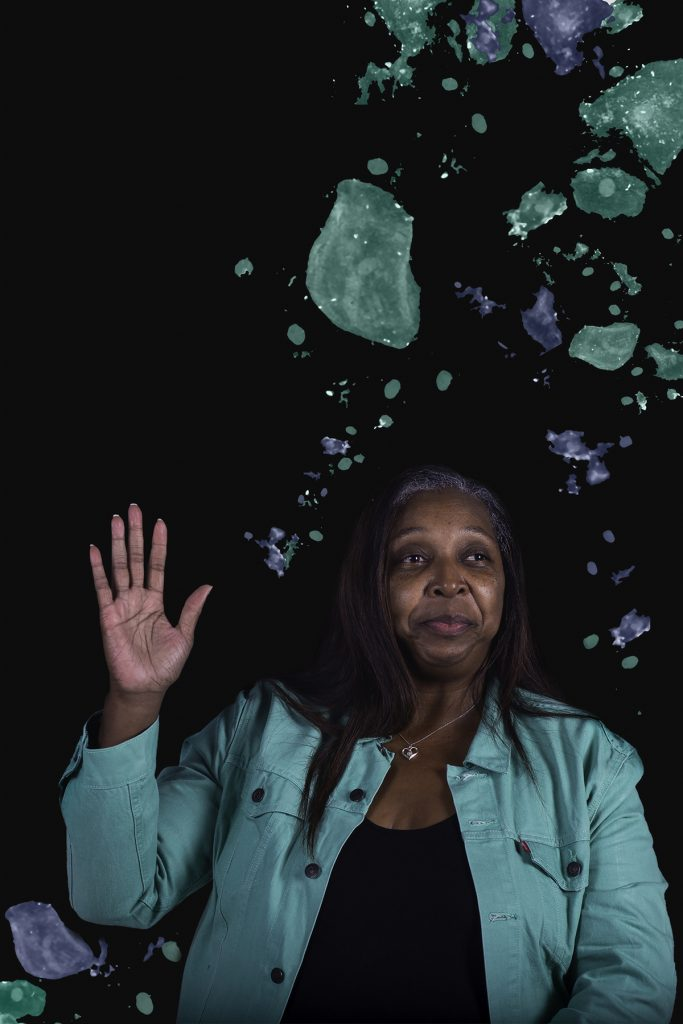 Portrait of a woman with her hand raised in front of a black background with green and blue cells.