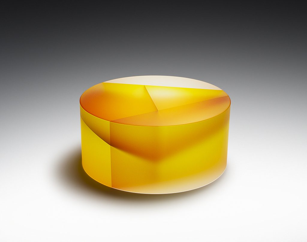 Large, yellow, cylindrical glass structure depicting segmentation of cells, displayed on a white background