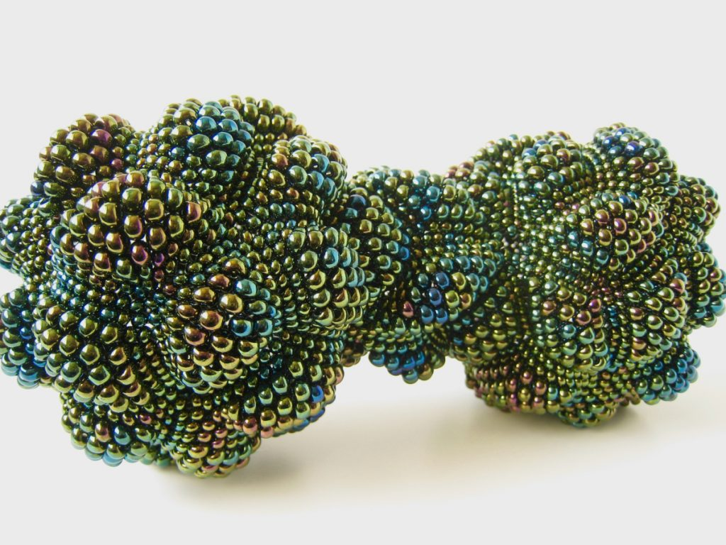 Dumbbell-shaped green work made of joined diamond-shaped beaded pieces.