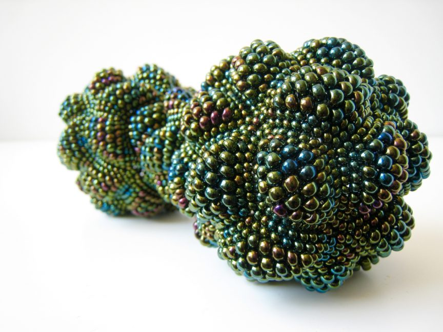 Multicolored green beadwork shaped like a dumbbell
